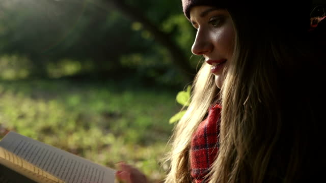 Closeup of beautiful young caucasian girl reading a book in the park at fall. video