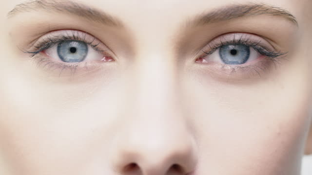 close-up of beautiful young woman with blue eyes - trattamento per la pelle video stock e b–roll