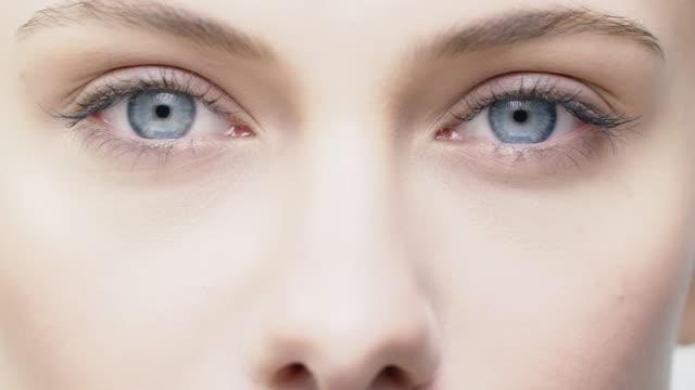 vídeos de stock, filmes e b-roll de close-up da mulher jovem e bonita com olhos azuis - skincare