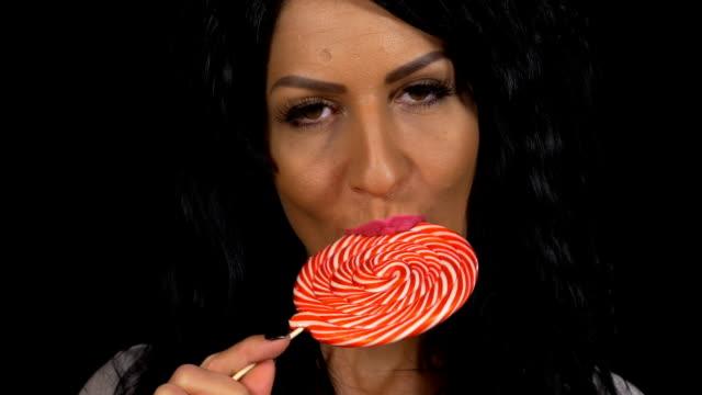 Closeup of beauty brunette girl eating a large lollipop on stick video