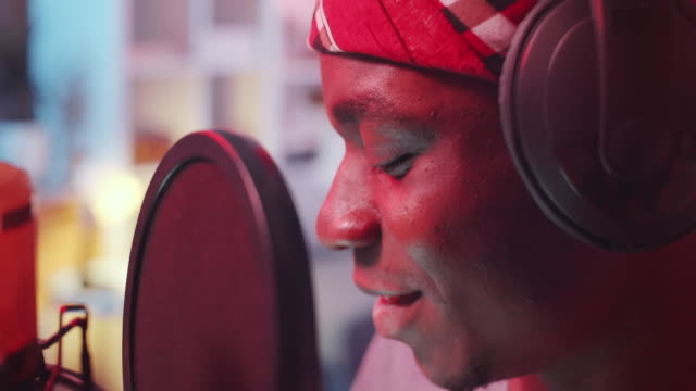 Close-Up of Black Hip-Hop Singer Recording Song in Home Studio