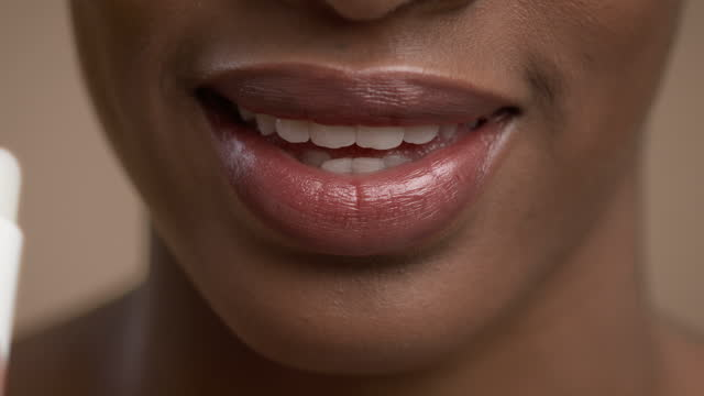 Closeup Of Black Woman Applying Lipstick Over Beige Studio Background Perfect Makeup. Closeup Of Black Woman Applying Lipstick And Smiling On Beige Studio Background. Cropped Shot Of Black Female Face While Lady Moisturizing Lips With Balm. Selective Focus lip balm stock videos & royalty-free footage
