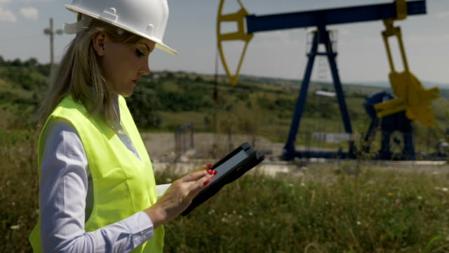 Closeup of blonde attractive engineer woman supervising oil pumping near a unit using digital tablet Closeup of blonde attractive engineer woman supervising oil pumping near a unit using digital tablet oil and gas stock videos & royalty-free footage