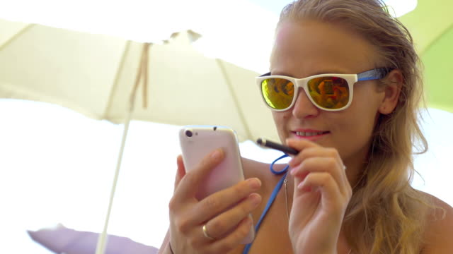 Close-up of blonde woman using smartphone