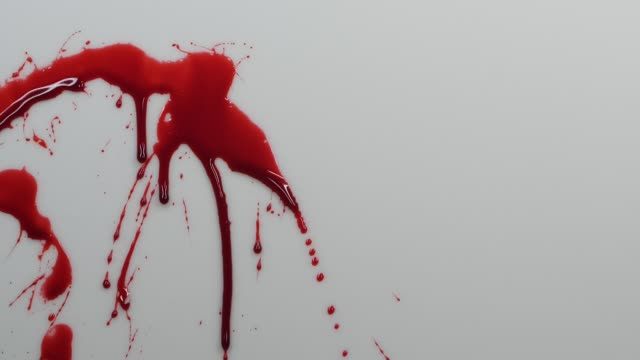 Close-up of blood splashing over grey surface