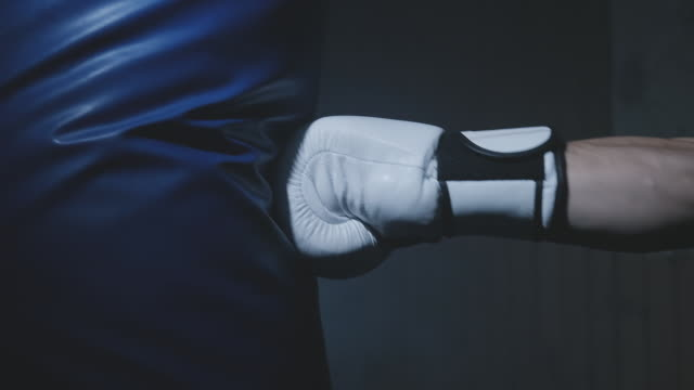 Close-up of boxer hits punching bag in dark gym. Young man training indoors.