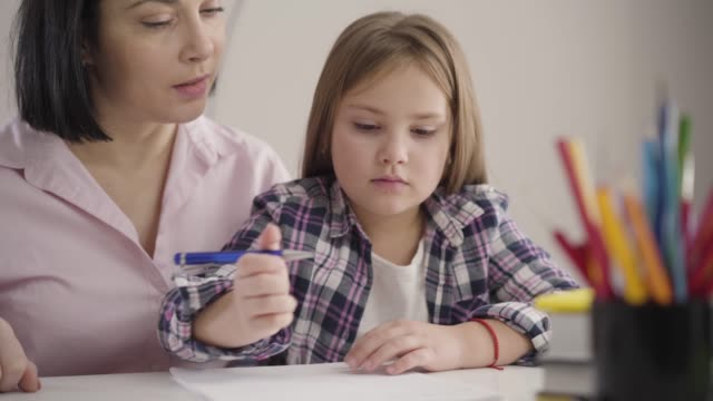 Close-up of brunette Caucasian woman sitting with daughter at the table and dictating. Wise parent helping schoolgirl with homework. Studying, education, family.