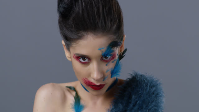 Close-up of brunette fashion model in bright stage make-up and feathers, that shows facial expressions. Fashion Video. Close-up of brunette fashion model in bright stage make-up and feathers, that shows facial expressions. Fashion Video. Slow Motion. 4K 30fps ProRes 4444 supermodel stock videos & royalty-free footage