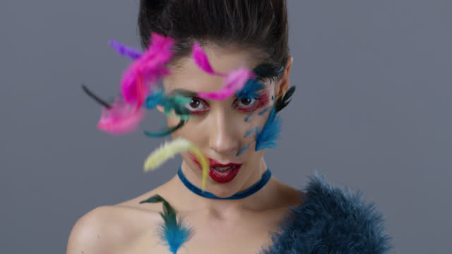 close-up of brunette fashion model in bright stage make-up and feathers, that shows facial expressions. fashion video. - топ модель стоковые видео и кадры b-roll