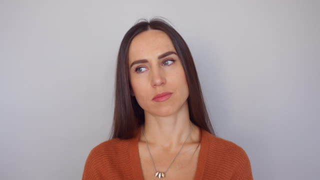 Close-up of brunette woman making different facial expressions showing boring look video
