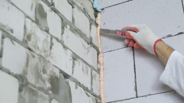 closeup of builder removing excessive mounting foam between walls - poliuretano polimero video stock e b–roll