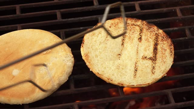 Close-up of burger buns with sesame seed frying on the grill