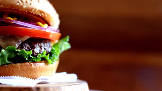 close-up of burger with copyspace rotating on wooden texture - hamburger video stock e b–roll