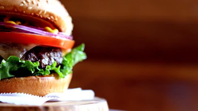 vídeos y material grabado en eventos de stock de primer plano de hamburguesa con copyspace girando sobre textura de madera - hamburguesa