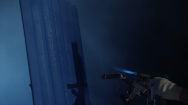 Close-up of burning blue metal siding. Dark background