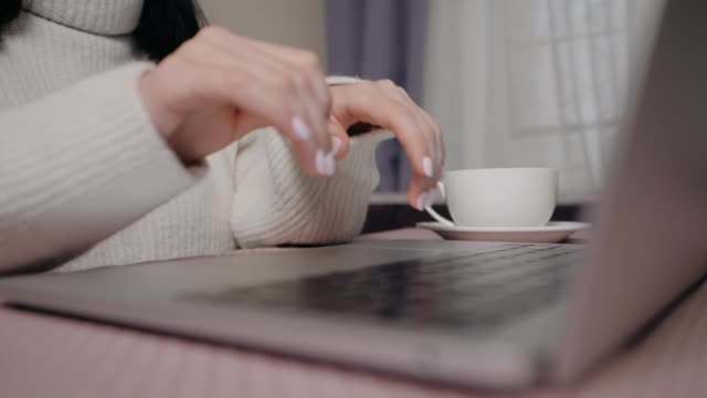 Closeup of business woman typing on laptop and drinking coffee. Female hands busy typing on keyboard. Freelance girl working at home in winter video