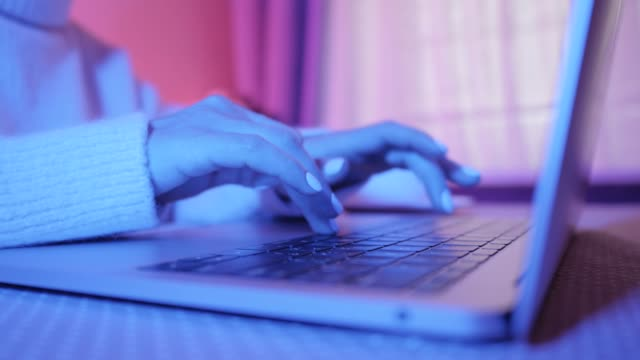 Closeup of business woman typing on laptop. Female hands busy typing on keyboard. Freelancer girl working at home in winter. Blue light in the room video