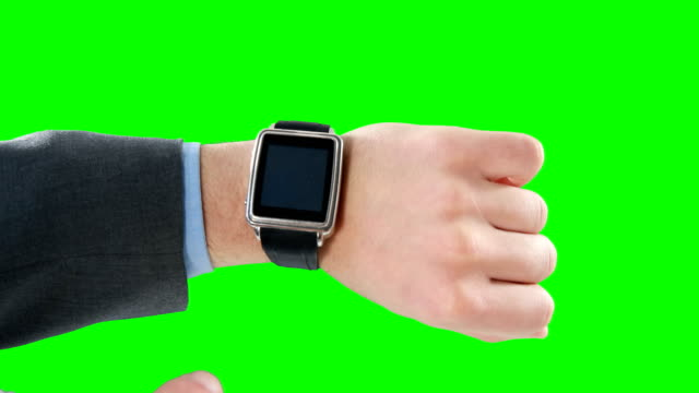 Close-up of businessman using smart watch Close-up of businessman using smart watch on green background wristwatch stock videos & royalty-free footage