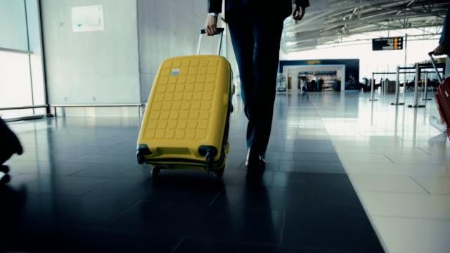 stockvideo's en b-roll-footage met close-up van zakenman wandelen onder reizigers menigte op luchthaven - zakenreis