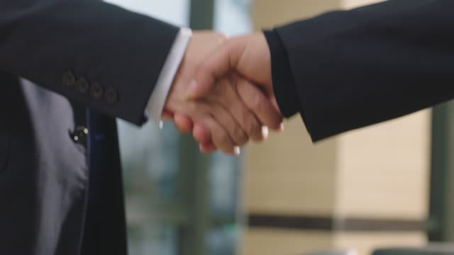 close-up of businessmen shaking hand & greeting in office - sud est asiatico video stock e b–roll