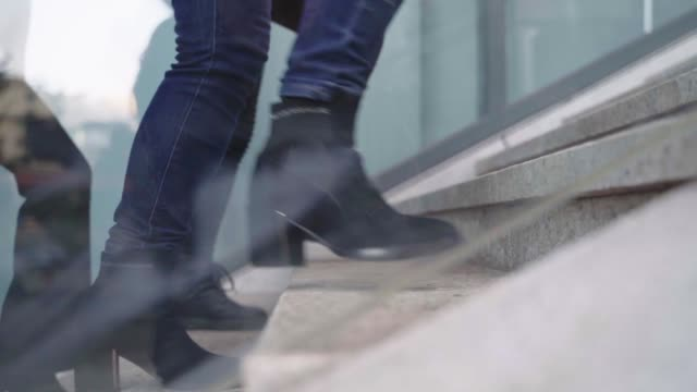 close-up of businesspeople walking down stairs outdoor - fianco a fianco video stock e b–roll