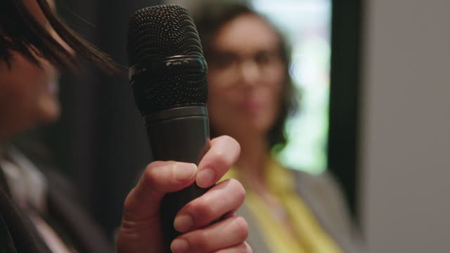Close-up of businesswoman holding microphone