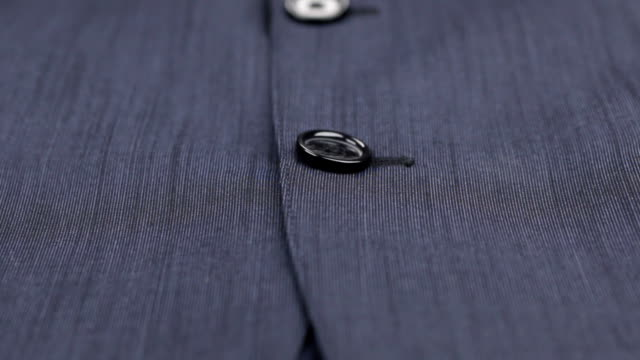 Close-up of buttons on a blue suit. Dolly shot. video