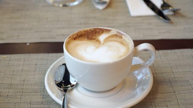 スプーンでソーサーに泡とカプチーノコーヒーカップのクローズアップ - ソーサー点の映像素材/bロール