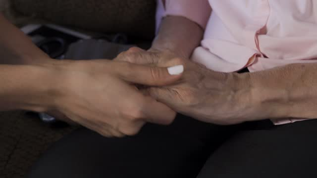 Close-up of caring nurse holding hands of senior woman at home