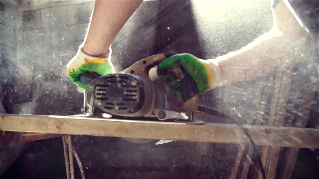 Close-up of carpenter cutting a wooden plank A man cuts a piece of wood with a hand held circular saw carpenter stock videos & royalty-free footage