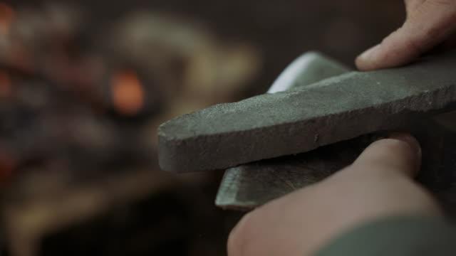 vídeos de stock, filmes e b-roll de o close-up do homem forte ocasional trabalha com o machado e a pedra de afiação perto da fogueira morna no acampamento na floresta deciduous selvagem. - afiado