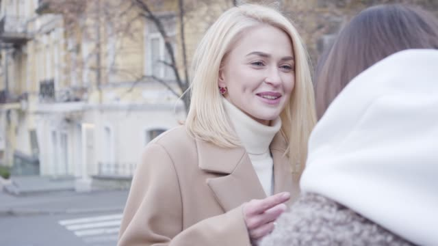 Close-up of cheerful blond Caucasian girl chatting with friends outdoors. Young woman talking and smiling as standing on city street.