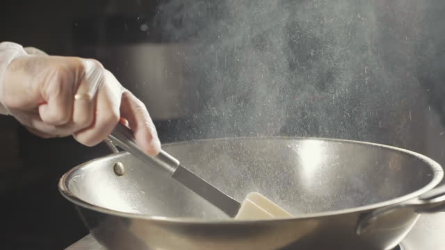 Close-up of chef cooking meat in wok pan. Meat fried in boil butter, slow motion video