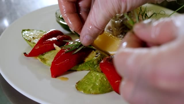 Close-up of chef decorating a dish with baked fish and vegetables with rosemary. Close-up of the chef decorating a dish with baked fish and vegetables with rosemary. Preparing and serving fish dishes in the restaurant. Slow motion. garnish stock videos & royalty-free footage