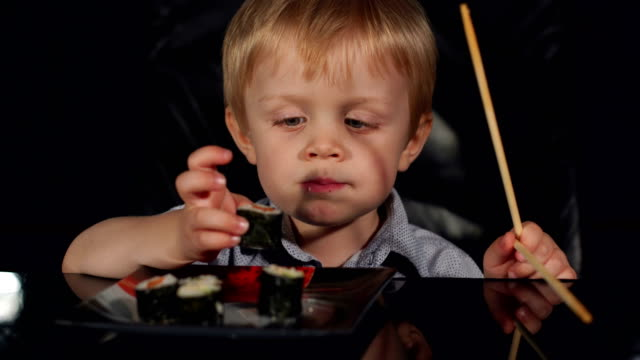 Close-up of child eating sushi on black background video
