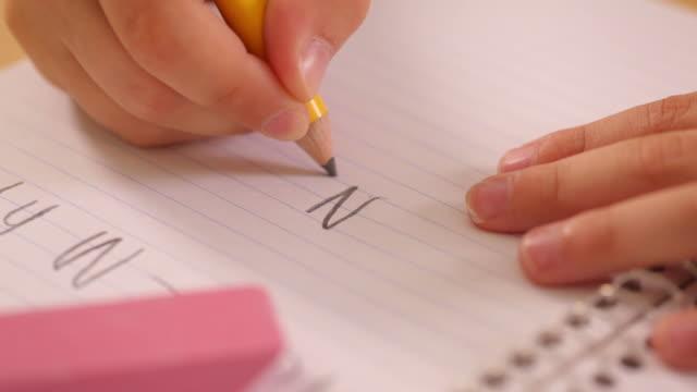 Primo piano del bambino scrivendo a scuola - video