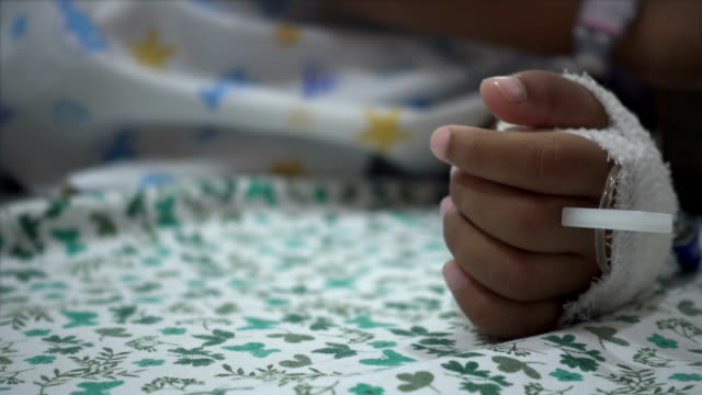 Close-up of childhood bandaged hand in bed hospital. Real time shot in treatment room. video