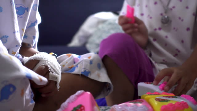 Close-up of childhood bandaged hand playing fruit toy with friendship in hospital. Relaxation time of young patient. Real time shot in treatment room. video