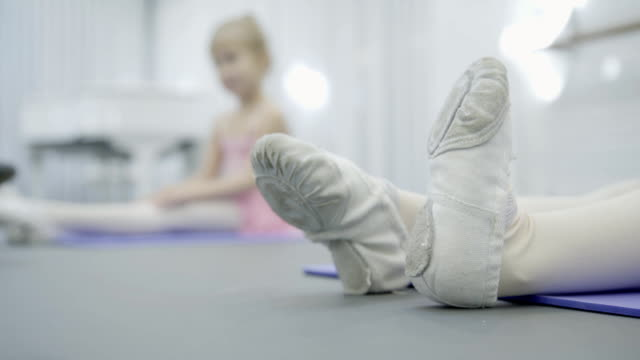 Close-up of children's legs in ballet dancers who do exercises video
