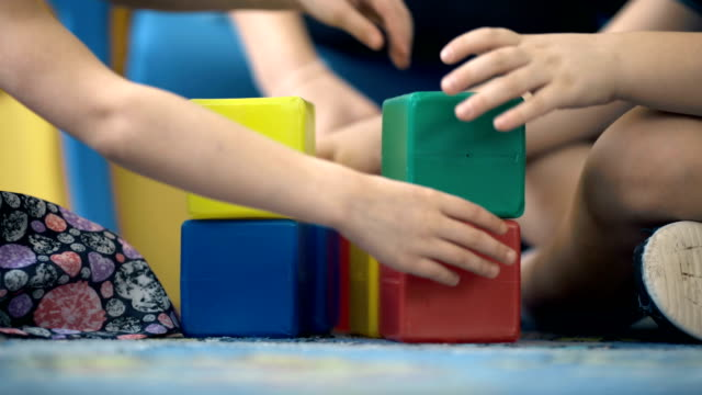 Close-up of child's hands playing with colorful plastic bricks