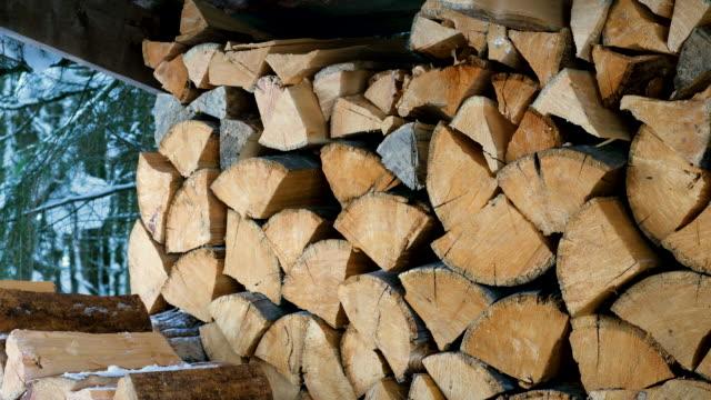 nahaufnahme von gehackten und gesägten baumstämmen, die in einem großen holzhaufen im hof gestapelt sind. brennholz für den kamin und denofen vorbereitet. 4k - brennholz stock-videos und b-roll-filmmaterial