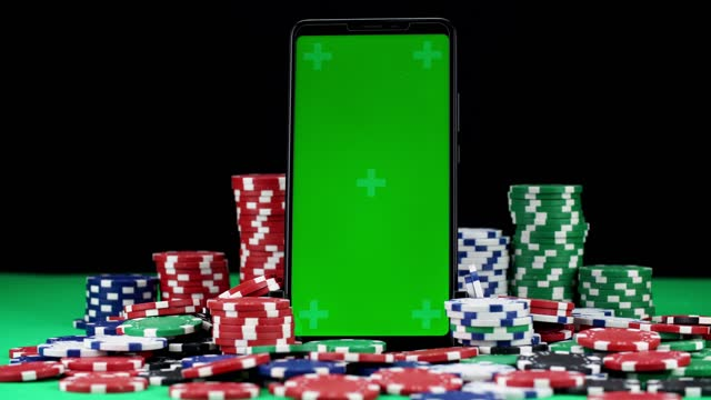 Close-up of chroma key mobile in vertical orientation among a pile of poker chips