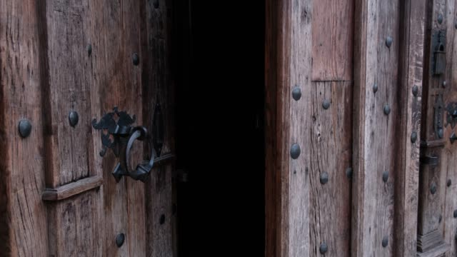 Close-up of closing old wooden door with metal handle in ancient medieval Catholic church.