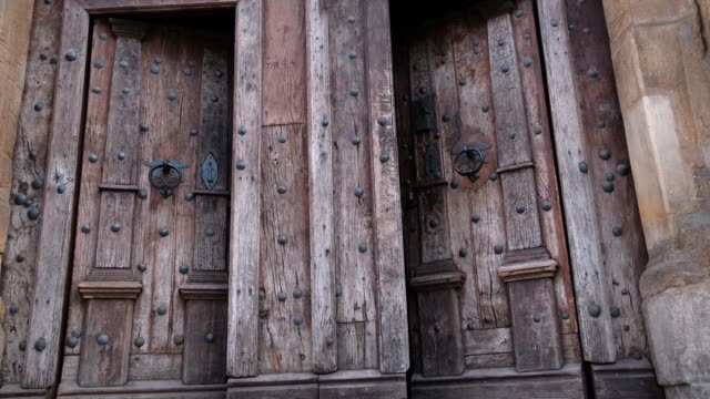 Close-up of closing two old wooden doors with metal handles in ancient medieval Catholic church.