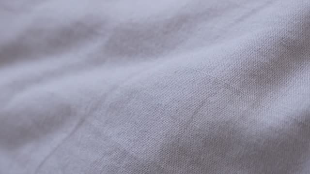 Close-up of cloth surface used as top bedding 4K 2160p 30fps UltraHD tilting footage - Slow tilt over fine cotton bed sheets texture in gray color 3840X2160 UHD video
