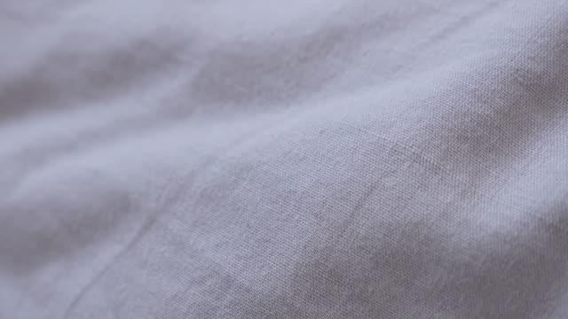 nahaufnahme der tuch-oberfläche verwendet als top bettwäsche 4k 2160p 30fps ultrahd kippbaren filmmaterial - langsam kippen über feine baumwolle bett bettwäsche textur in grauer farbe 3840 x 2160 uhd video - teurer lebensstil stock-videos und b-roll-filmmaterial