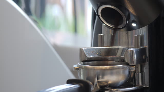 Close-up of coffee grinder grinding freshly roasted make beans into a powder