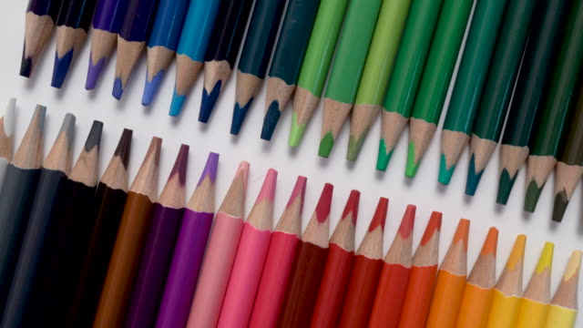 Close-up of colored pencils row on white background
