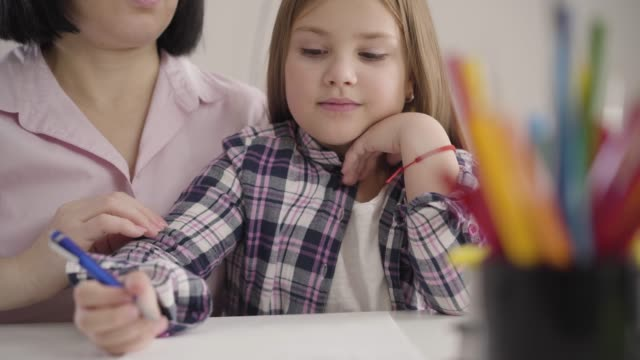 Close-up of concentrated Caucasian brunette girl writing in exercise book as her unrecognizable mom dictating at the background. Schoolgirl doing homework with mother indoors.