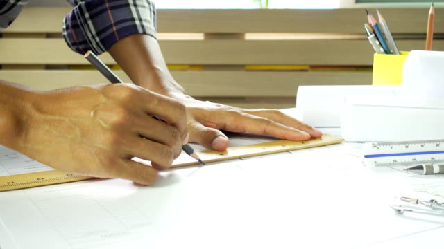 Close-up of confident architect male in casual wear working on desk. Concept of building working on house project.